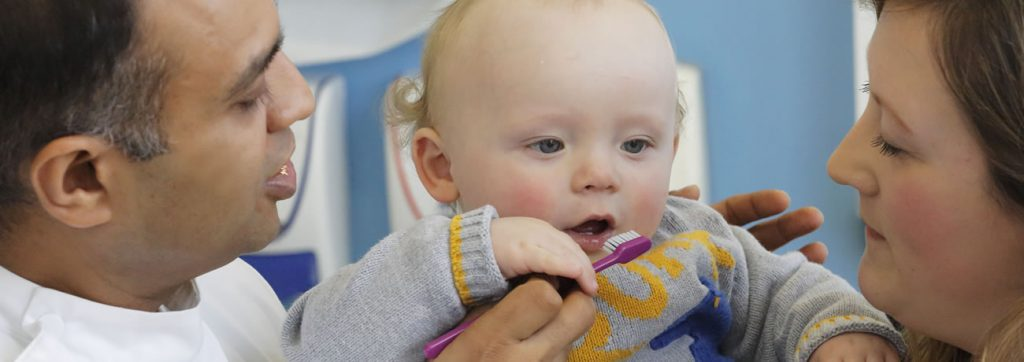 Small child using a tooth brush helped by the dentist and his mum